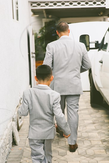 boy and man  in gray formal suit jacket walking beside white car during daytime photo