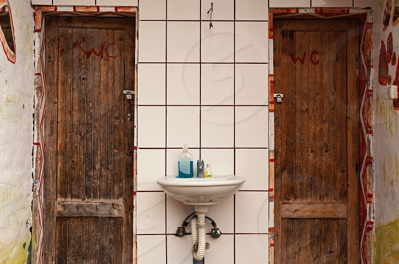 Two doors of two WC old retro style decorated closed and locked.  photo