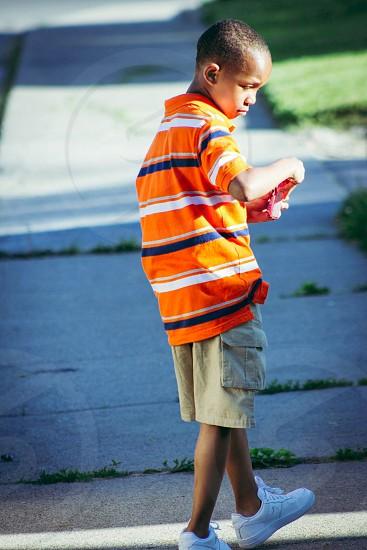boy wearing orange blue and white polo shirt and grey cargo shorts walking during daytime photo