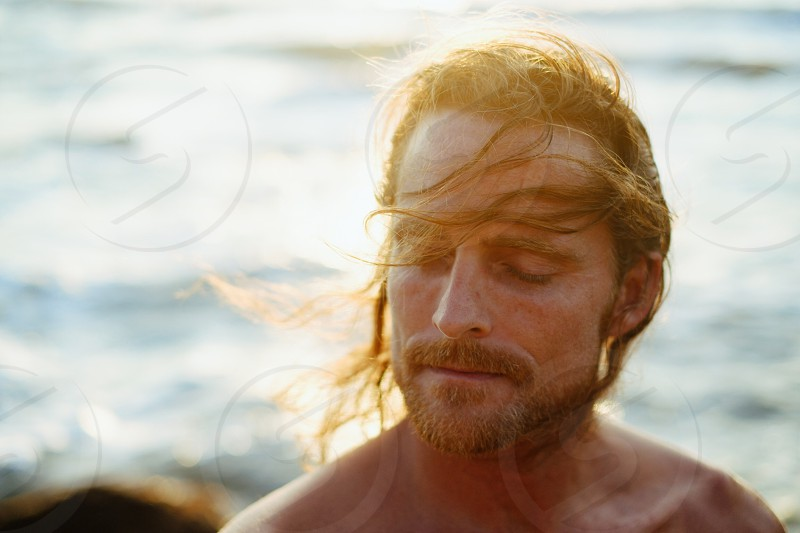 Summer mood man young sunlight flare face joy cheerful closed eyes dream tranquil serene calm sunset ocean sea long hair photo
