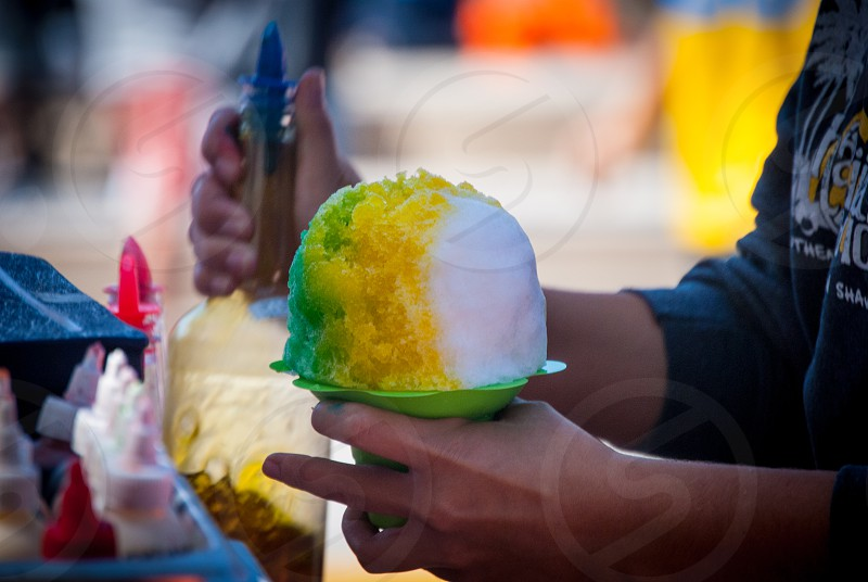 Snow cone shaved ice frozen ice cone hand green treat snack fair photo