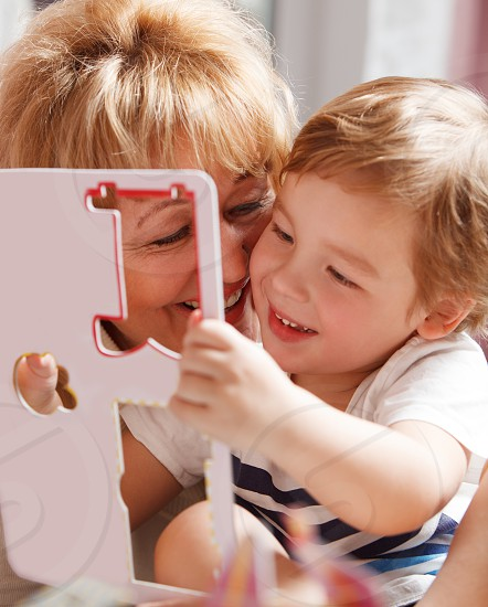 Happy family of grandma and grandson having fun during puzzle solving photo