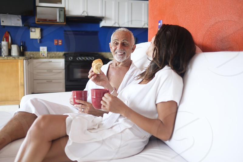Couple in white bathrobes enjoying mini breakfast with coffee mugs and baking goods in their apartment photo