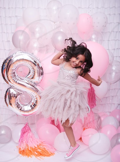 girl in gray spaghetti strap ruffled midi dress with pink low top sneakers jumping beside silver s balloon surrounded by white and pink balloons photo