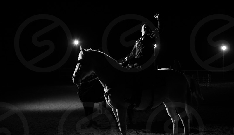 A black and white photo of a man on horseback having fun. photo