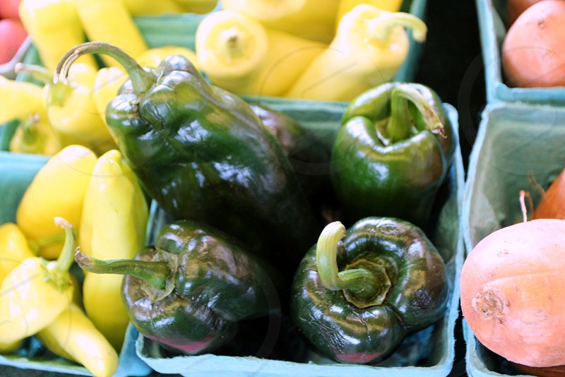 Dark green peppers in carton at farmers market photo