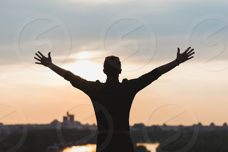 Young man standing with arms stretched looking at sunset photo