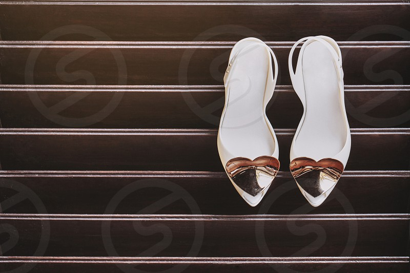 Women's ivory pump shoes adorned with shiny brushed heart decoration at the shoes head is hanging on the wooden lath wall copy space or space for text on the left side photo