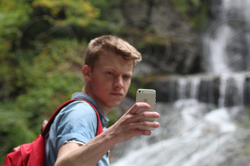 man wearing a grey shirt and red backpack holding up a phone photo