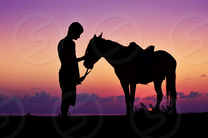 man with a horse silhouette on flat land under a purple and orange sunset sky photo