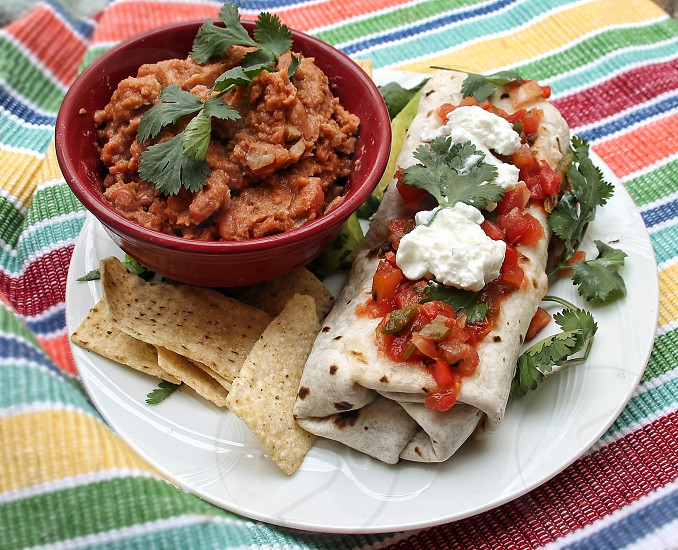 Mexican food on a festive place-mat: Burrito salsa and sourcream with refried beans and tortilla chips. photo