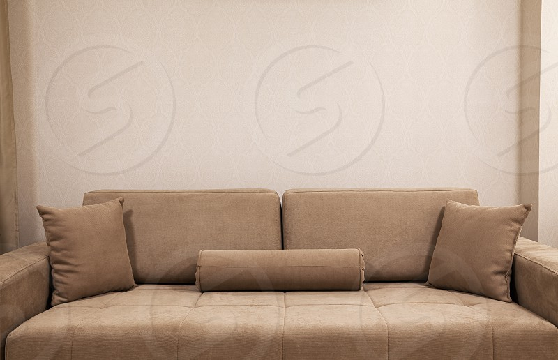 Modern and new couch in front of wall with decorative wallpapers. photo