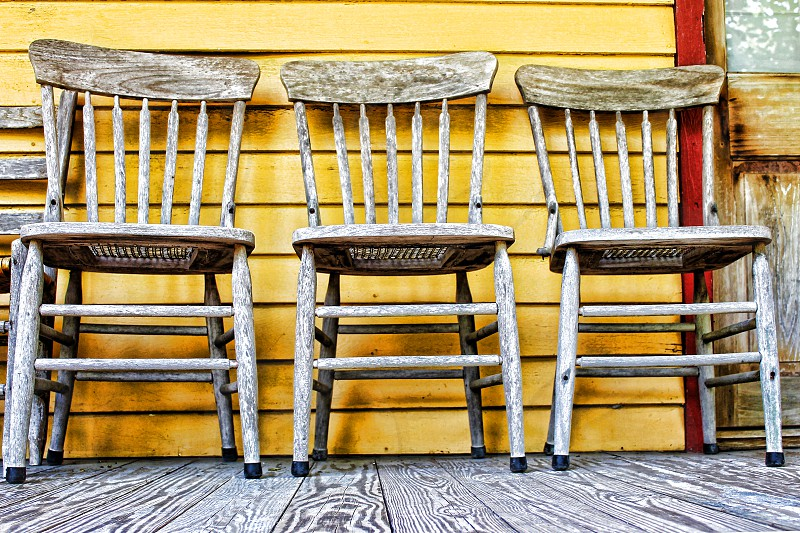 Close-up of three rustic wooden chairs on a front porch photo