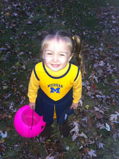 little girl dressed up for Halloween in a UofM cheerleader costume for trick or treating photo