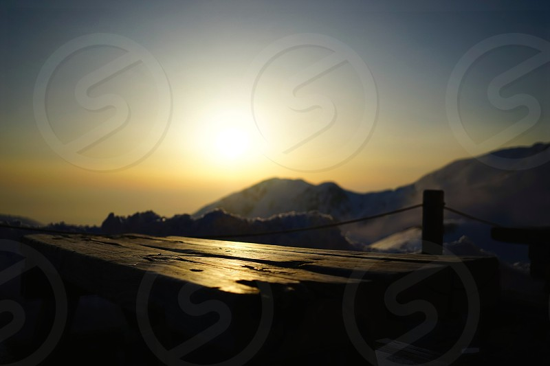 wooden table with yellow sunrise and snow mountain in background photo
