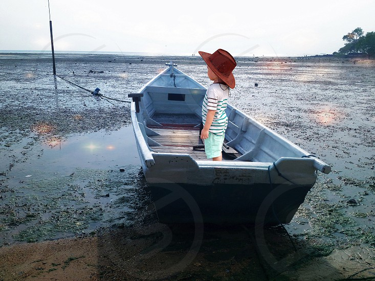 kid in brown cowboy hat white and black striped t shirt and green shorts standing on grey fishing boat in shallow water with green plants looking out at bay under white cloudy sky photo
