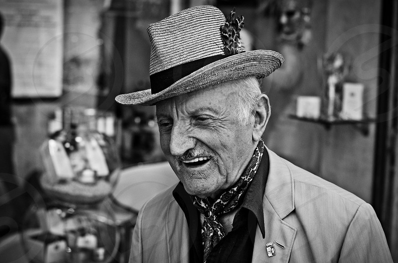 smiling man in coat wearing fedora hat in grayscale photo