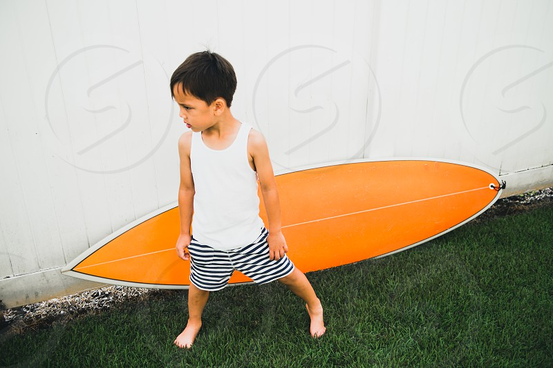 A young boy checking out his new surf board. photo