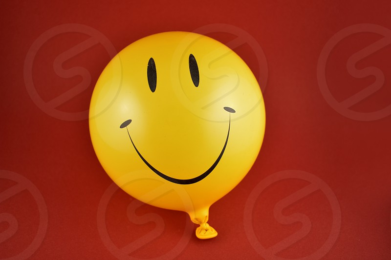 Happy emoji balloon. Yellow balloon photo. Smiley inflatable balloon isolated on a red background. Laughing party balloon photo