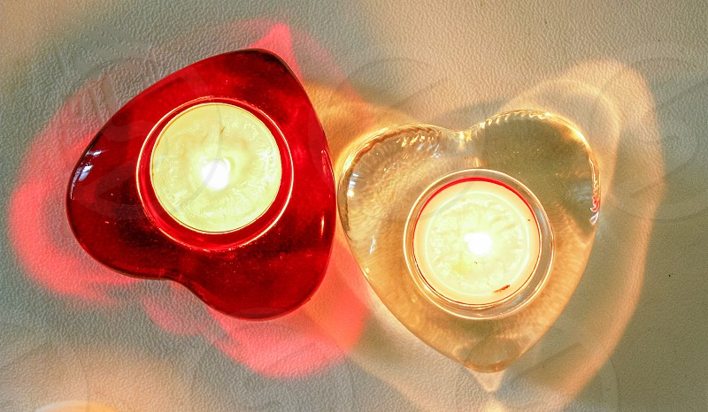 white burning candles in red and yellow heart shaped containers photo