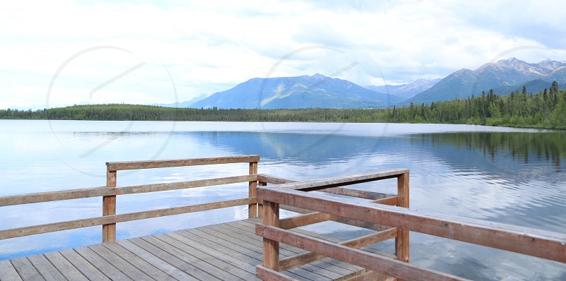 mountains over lake with pier photo