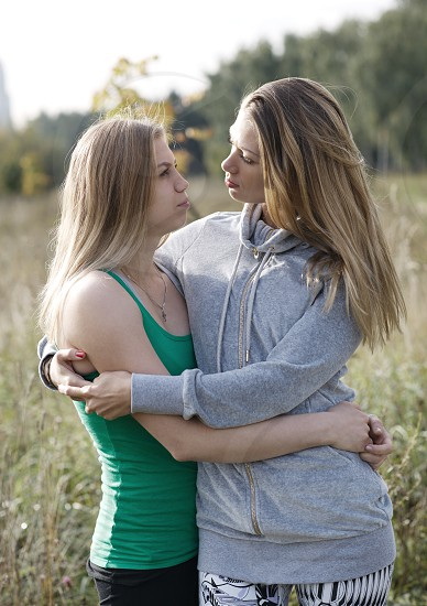 Two loving sisters comforting each other hugging in a close embrace as they stand outdoors in the countryside photo