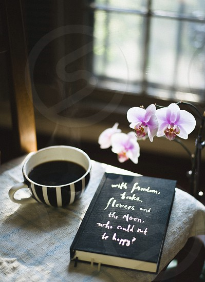 white black striped coffee mug and black book near window photo
