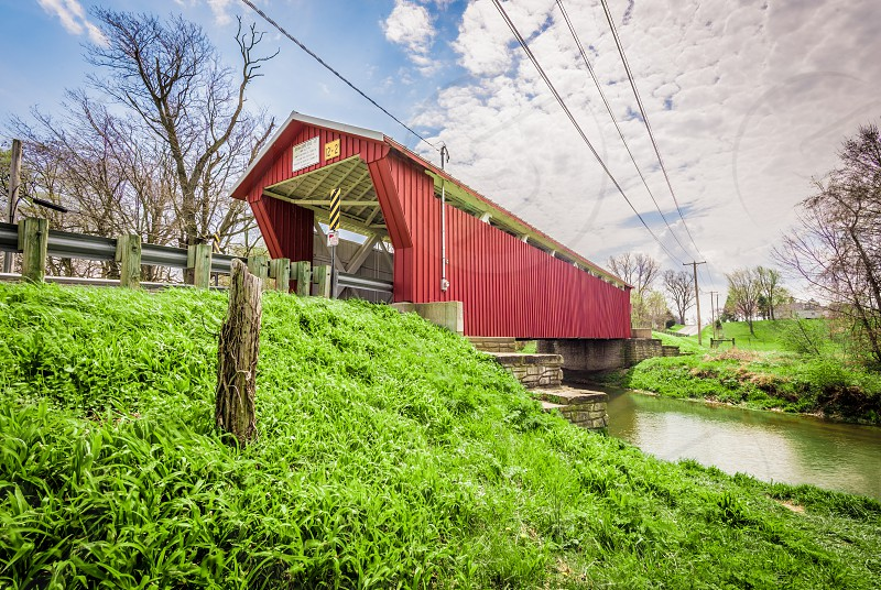 Red covered bridge over a stream in Ohio in the spring time. photo