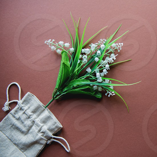 Top view of plastic flower bouquet lily of the walley on brown background photo