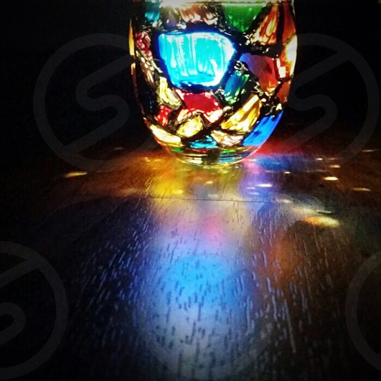 Candle glass holder painting and the light reflection..  photo