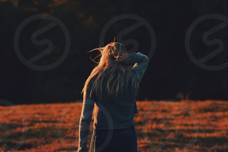 selective focus photography of woman's back holding her hair photo
