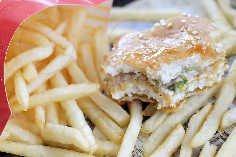 Close-up of half-eaten burger with fries. Shallow depth of field. photo