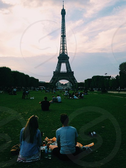 man and woman sitting on green grass looking at the eiffel tower photo