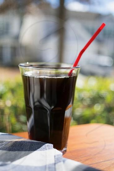 Coffee glass red straw green background bokeh photo