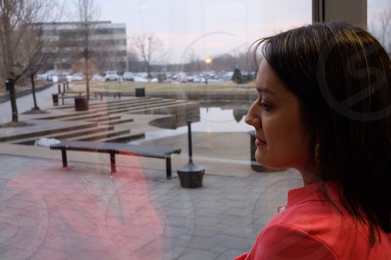 women with brown hair in coral polo shirt looking out window to plaza photo
