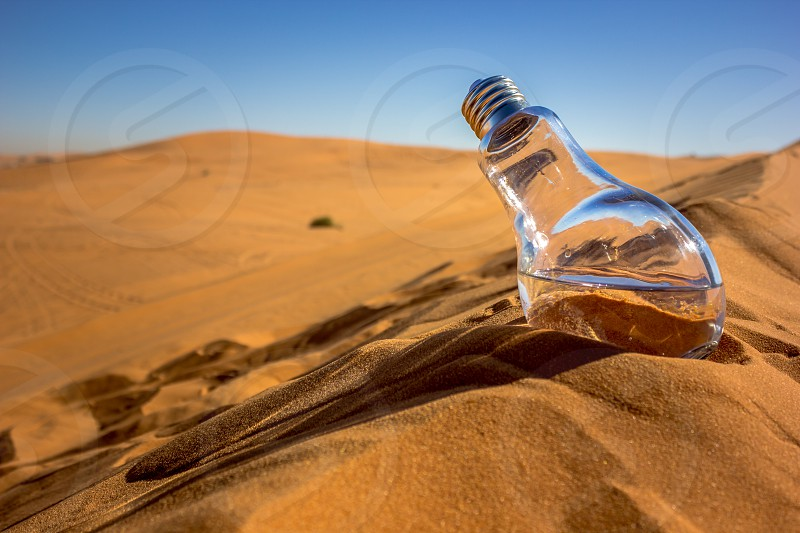 photo of light bulb with water on brown desert hill under clear blue sky photo