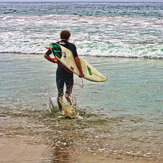 Seen from behind a surfer in a wetsuit holds a board and wades into the ocean. photo