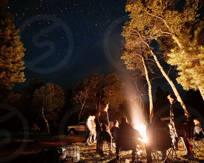A group of people enjoy a bonfire under the stars. photo