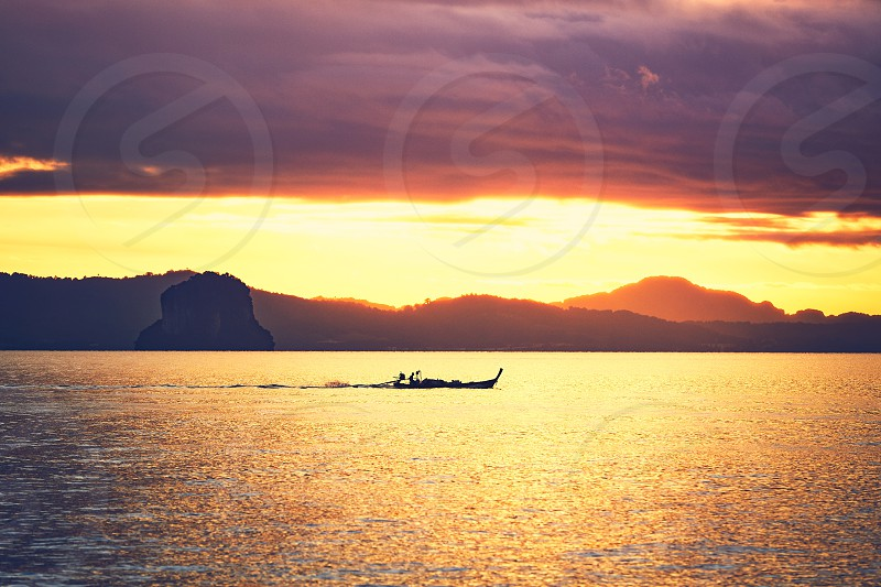 Amazing sunrise on the sea. Silhouette of a small fishing boat against tropical islands between Phuket and Krabi in Thailand photo