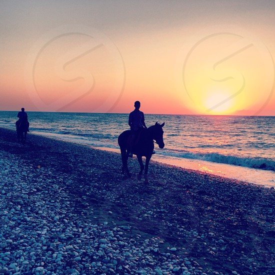 Horseback riding on the beach during sunset in Rhodes Greece  photo