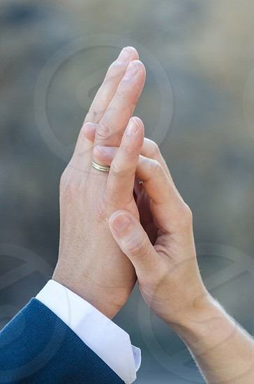 man wearing silver band ring and woman holding hands photo