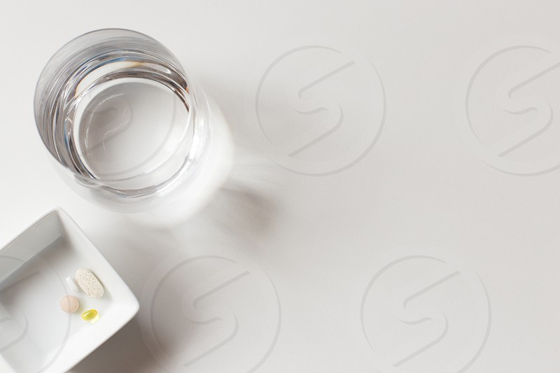 A glass of water and some medication with a white background and copy space photo
