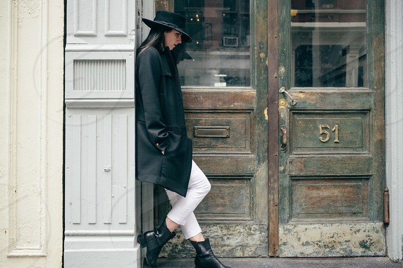 woman in black coat leaning on wall photo