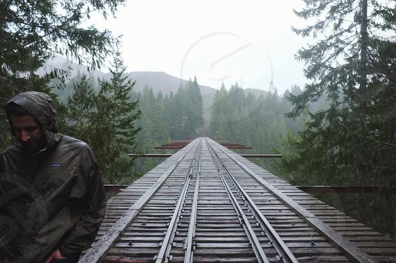 man walking on brown wooden train rail wearing black leather jacket photo