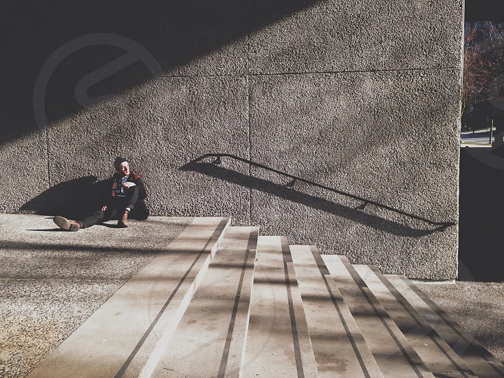person sitting beside staircase photo