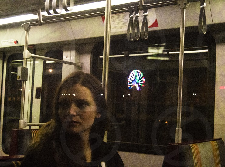 A reflection of my friend off a train window with a ferris wheel in the background. photo