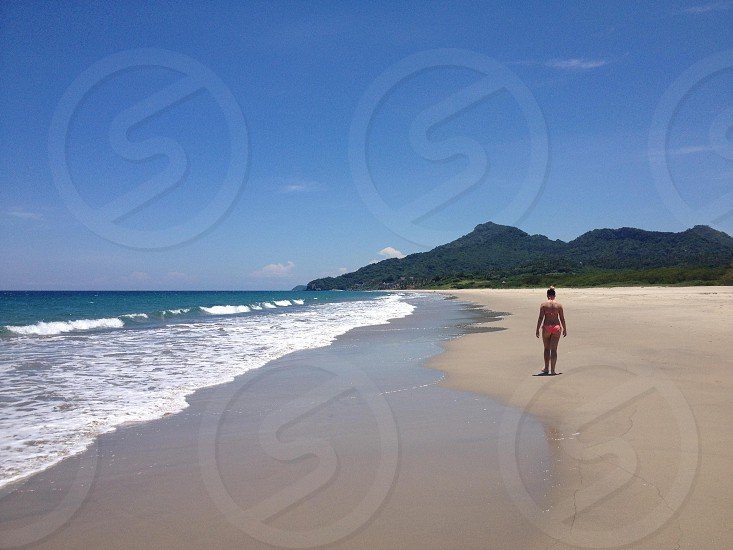Girl walking on beach with mountain jungle in the distance. Mexico blue sky ocean and waves. photo