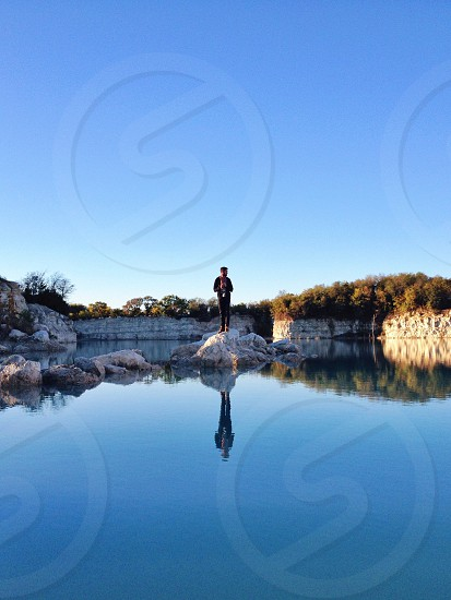 man on a rock in the water photo