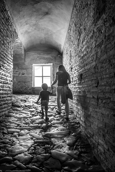 woman and boy walking on a stone floor building photo