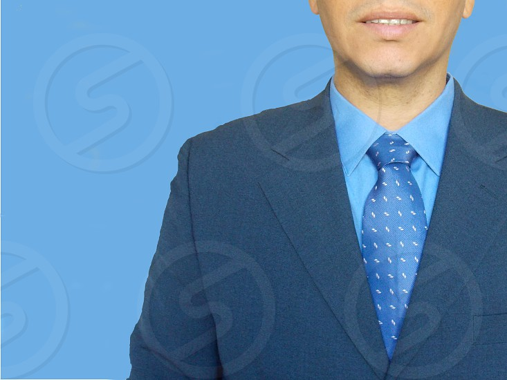 man in black blazer and blue shirt and tie photo